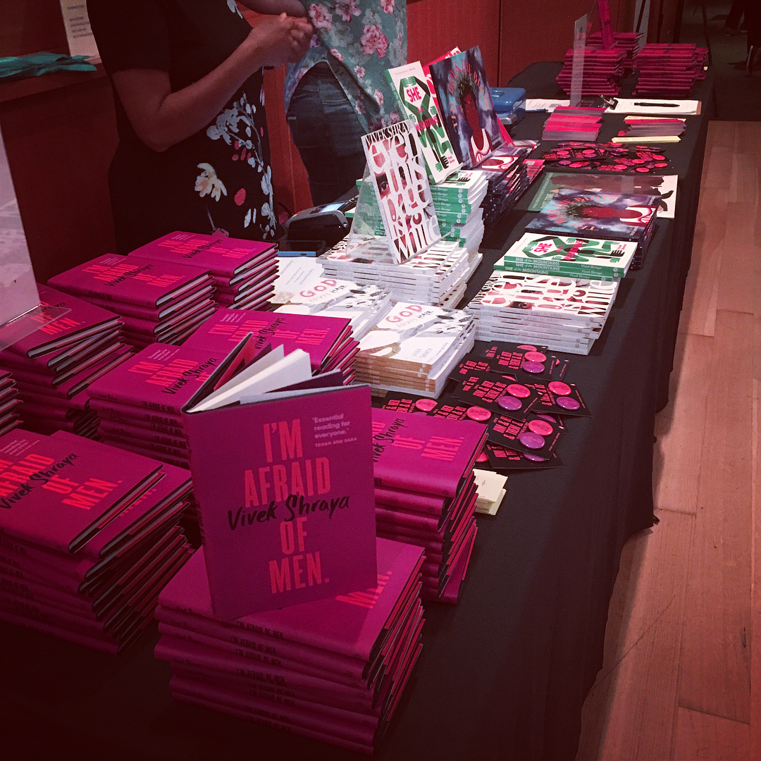 A photo of the vendor table at the launch of I'm Afraid of Men, covered in many copies of Vivek Shraya's books, records, and children's books. There are also lots of I'm Afraid of Men buttons and bookmarks.