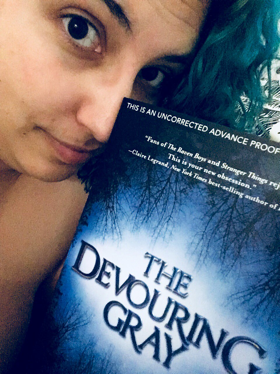 A selfie of me with green hair, holding a physical ARC of The Devouring Gray, by Christine Lynn Herman.