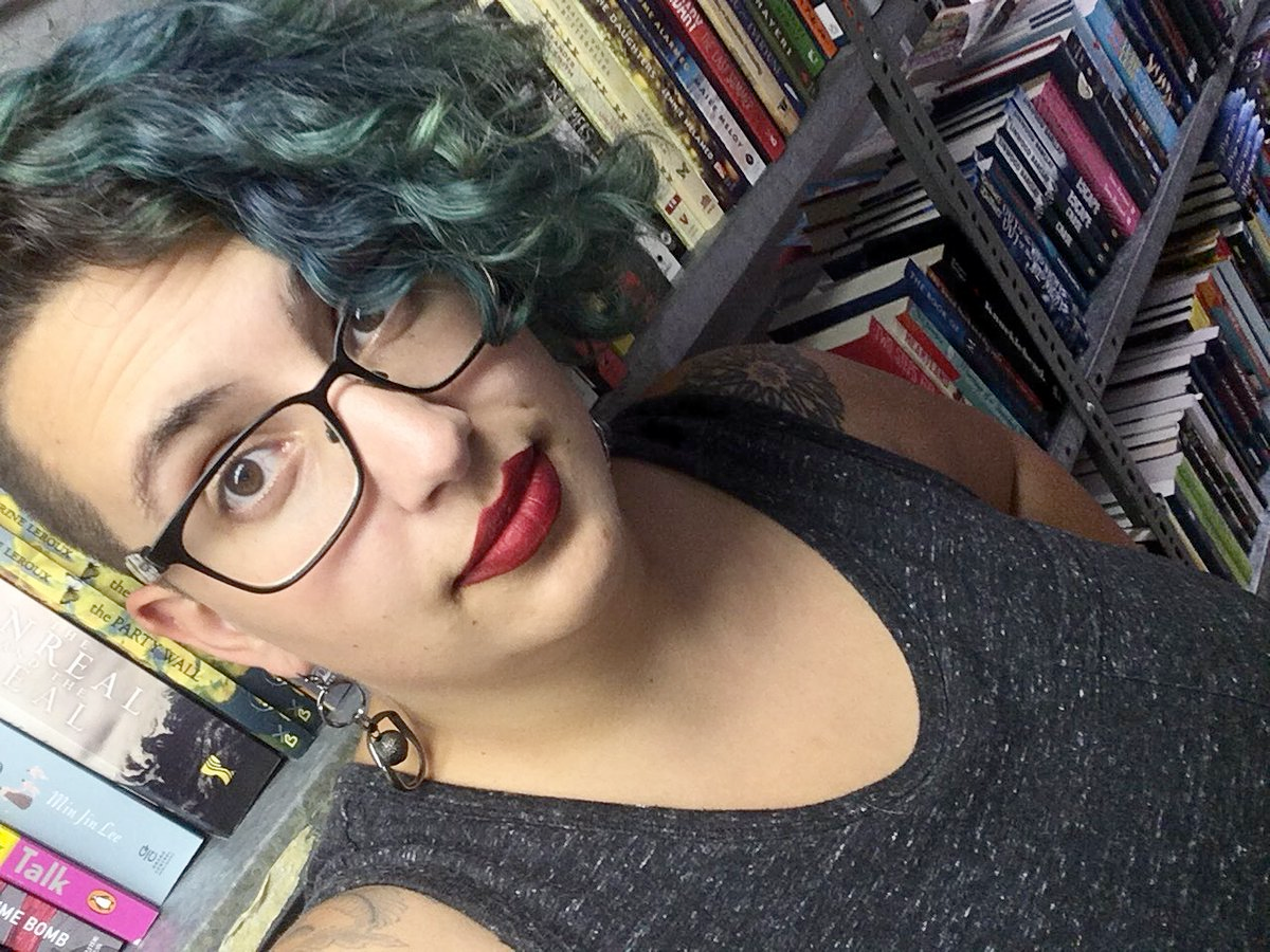 This image is a selfie of me with teal hair and red lipstick. It's taken in the basement of the book shop where I work, so there are shelves of overstock books in the background.