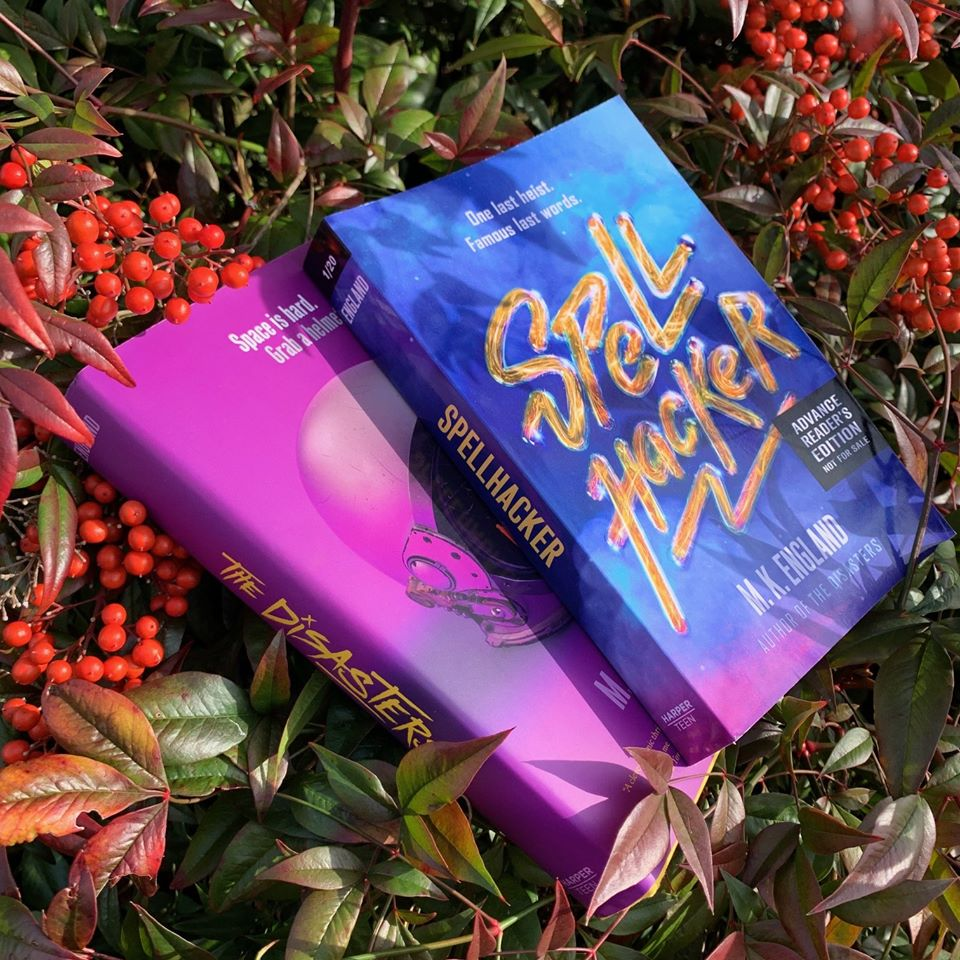 Two books laying in some festive foliage. Underneath, a hardback of The Disasters, a space helmet on a pink background. On top, an ARC of Spellhacker, a purple galaxy print cover with sparkly gold text.
