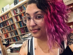 A selfie of me in the bookshop where I work. I have medium complexion white skin, pink curly hair that is shaved on the right side and has dark roots, clear plastic frame glasses, and no makeup. I'm wearing a black tank top and a grey sports bra, and tattoos are visible on my shoulders. Bookshelves are visible in the background.