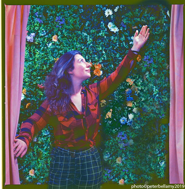 A stylized photo of Chana Porter, looking upward, arm reaching up. Theatre curtains frame the image. The background is foliage with flowers.
