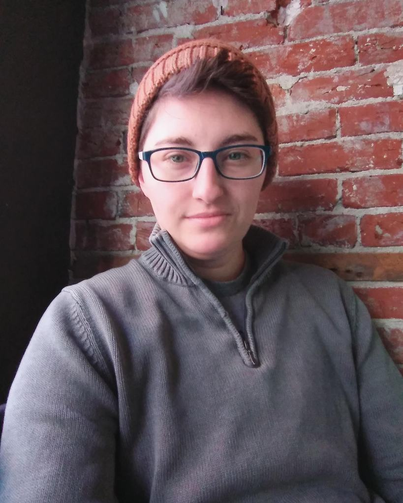A non-binary person in front of a brick wall. They are wearing an orange knit cap, black-rimmed glasses, and a grey sweater. They smile slightly, and have short cropped hair.