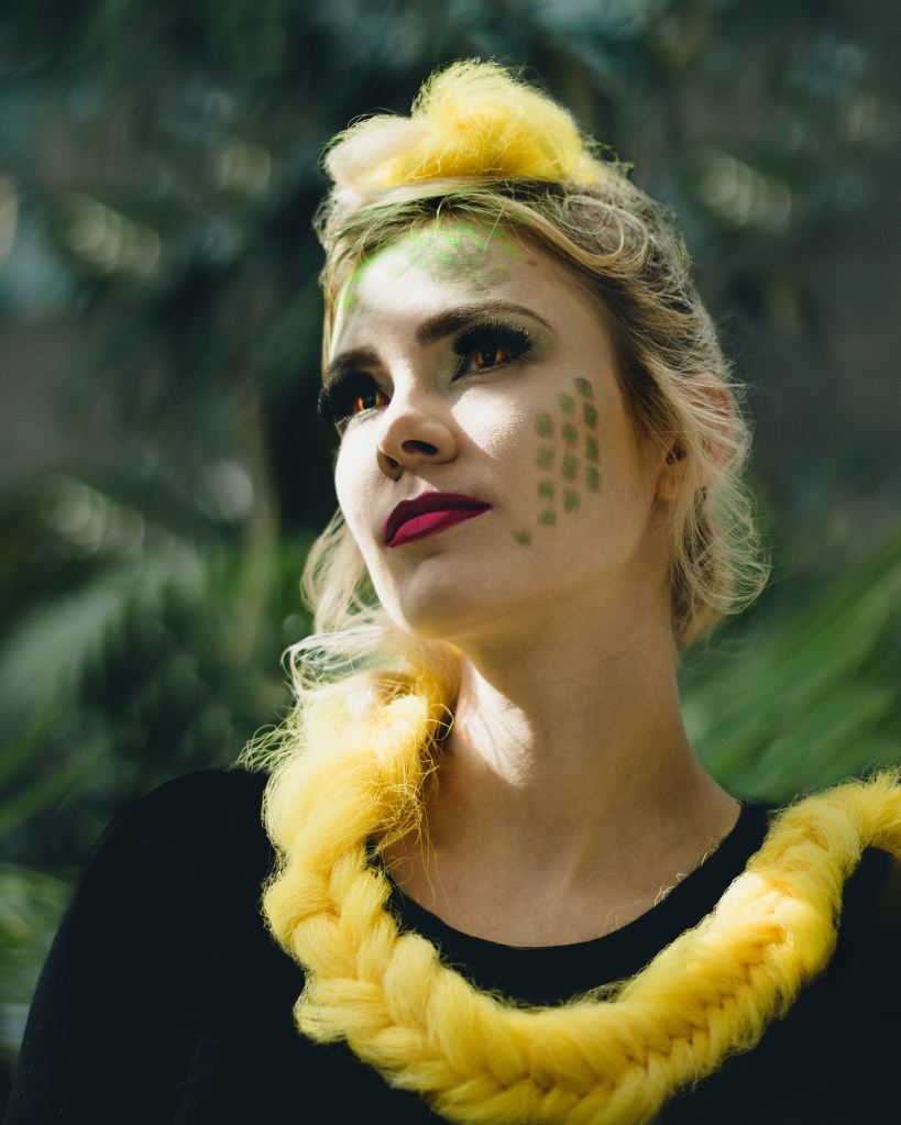 An image of a white person with red lipstick, snake eye contacts, and green scales airbrushed onto their cheek. Their hair is bright yellow and long, wrapped around their neck in a braid.