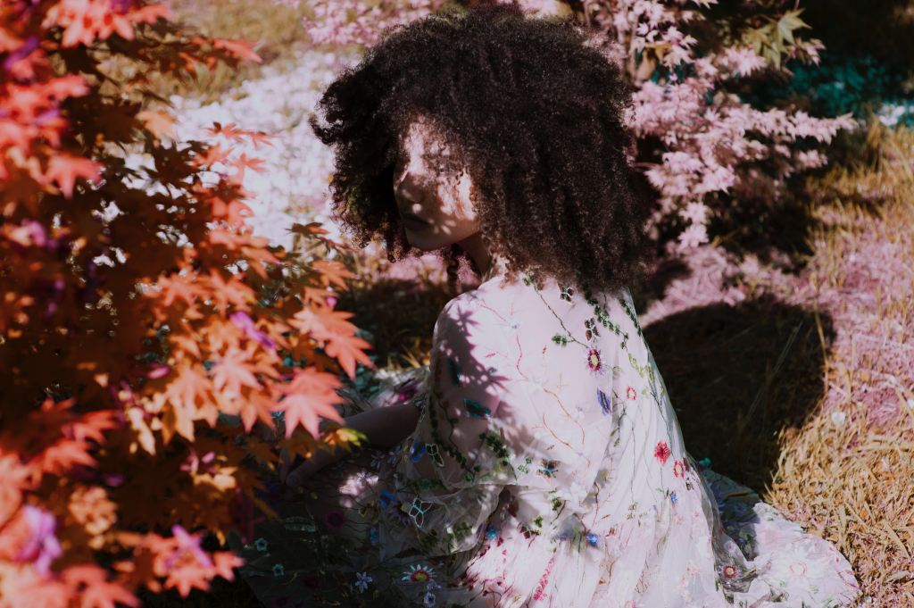 A feminine figure crouches in some foliage, face partially obscured by shadows.