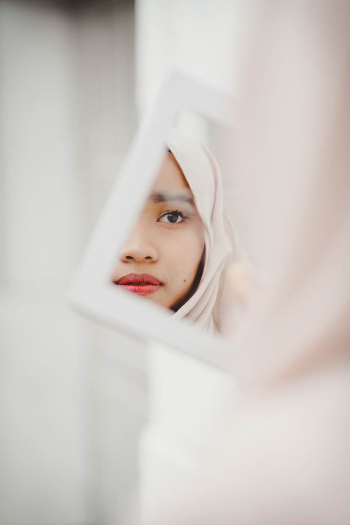 A person's face, partially obscured, wearing a headscarf and reflected in a mirror.