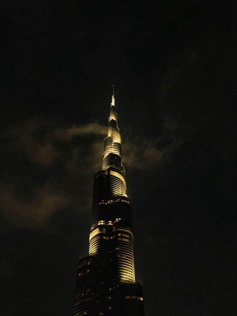 A tower, lit up at night, reaching into the clouds.