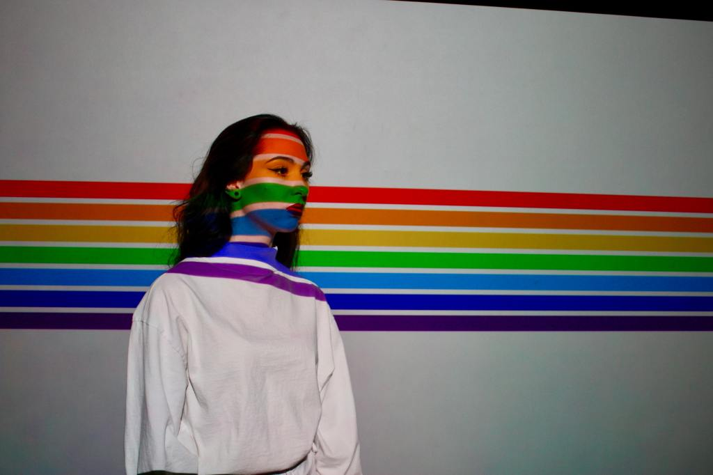 A person standing on a white background with rainbow stripes. The stripes cross their face as well.