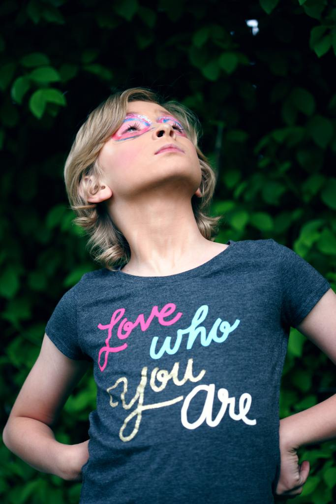 A young person with their hands on their hips, looking upward. They have elaborate eye makeup on, and a t-shirt that says, Love you who are.