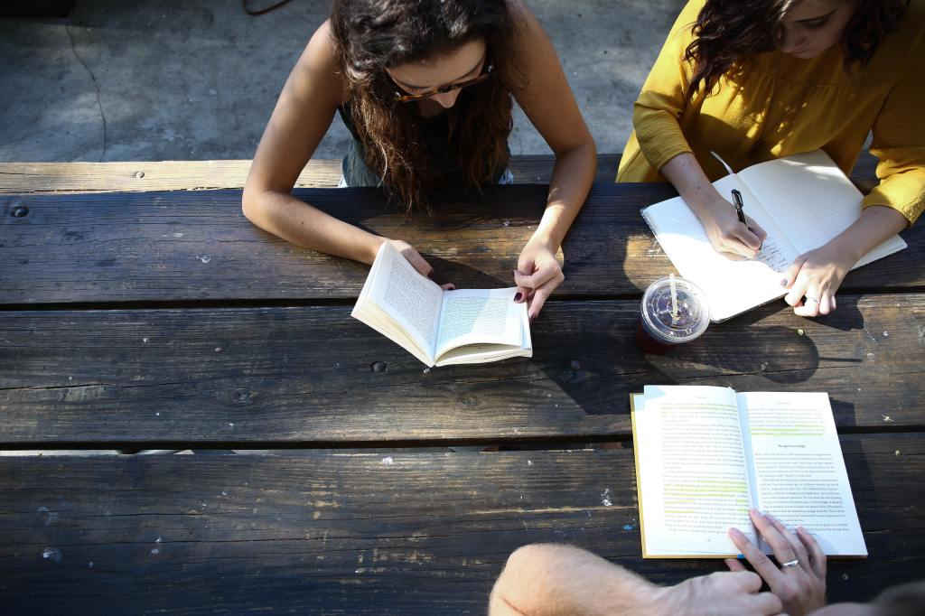 A group of people sitting at a wooden table with notebooks, a plastic coffee cup, and a book with highlighting inside. They look like friends collaborating on a project.
