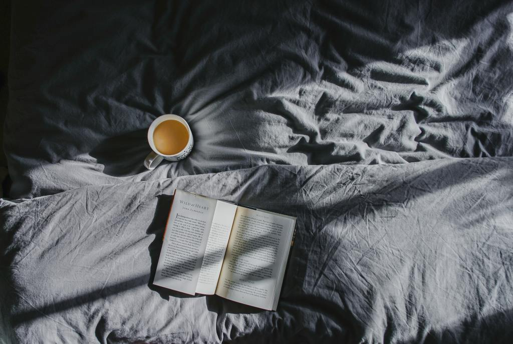 A coffee and an open book on bedsheets.