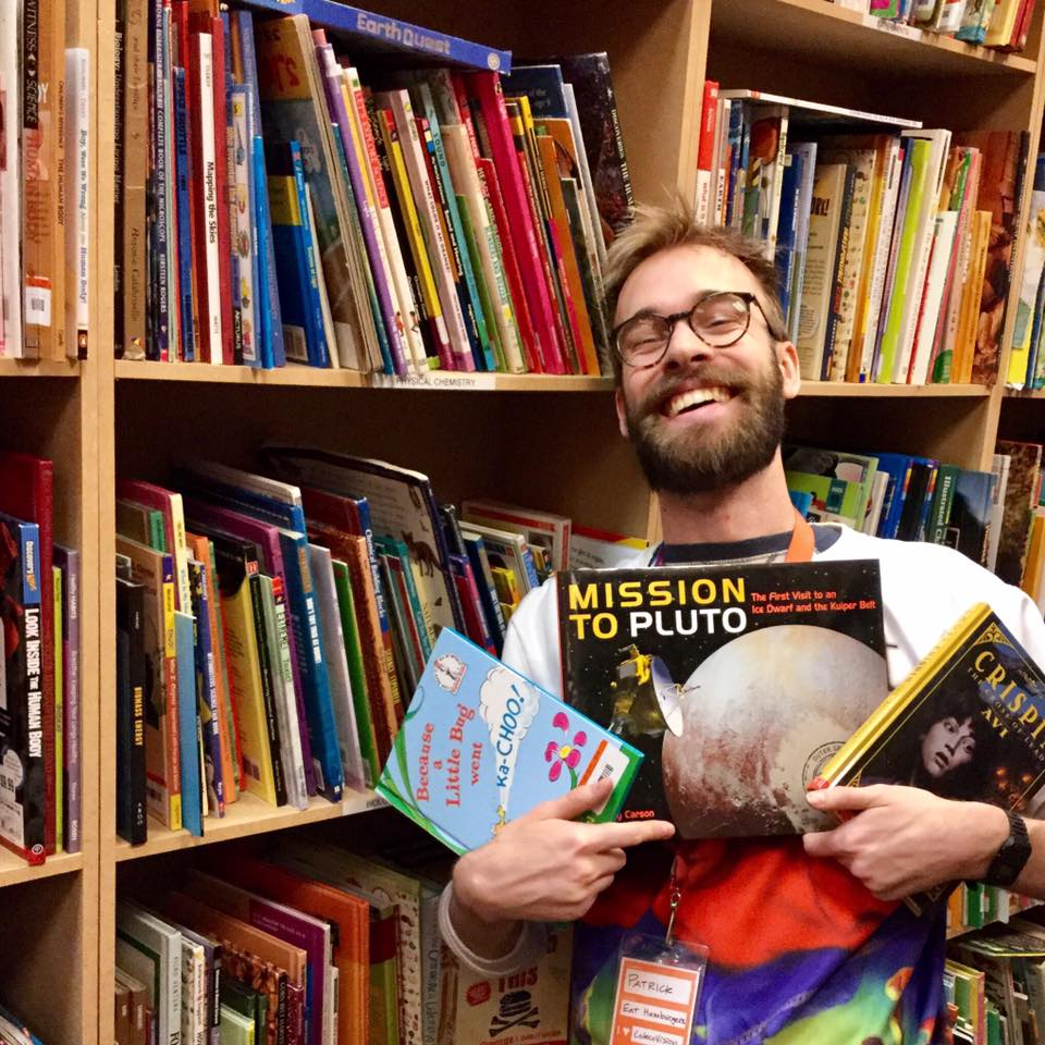 A bearded person stands in front of shelves of picture books with their arms full of books. They are laughing.