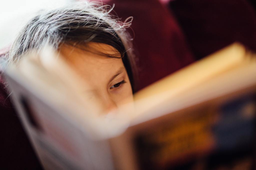 A close up of a child reading a book, one eye visible, and the book large and out of focus in the foreground.
