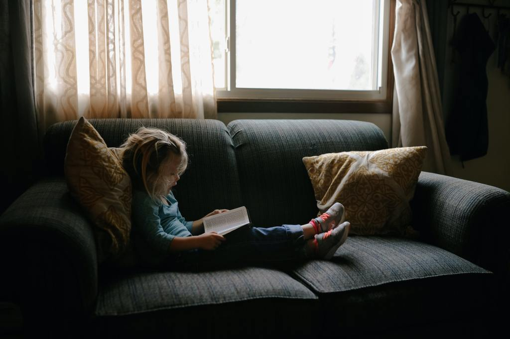 A small child reading on a couch.
